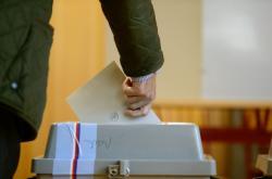 Volič vhazuje obálku do volební urny v Praze.