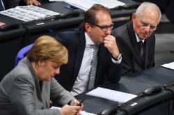 Wolfgang Schaüble (vpravo) se dívá směrem ke kancléře Merkelové