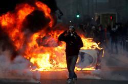 Demonstrant a hořící auto v Paříži