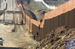 Lidé přelézají plot mezi Mexikem a USA