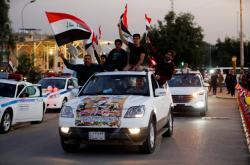 Řidiči oslavují vjezd do tzv. Zelené zóny v Bagdádu