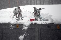 Němečtí vojáci odklízejí sníh ze střechy domu v bavorské obci Strub blízko Bischofswiesenu