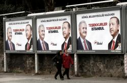 Lid v Istanbulu míjejí plakáty AKP s tvářemi prezidenta Erdogana a expremiéra Yildirima