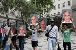 Demonstranti v New Yorku s podobiznami Epsteina