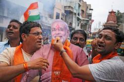 Lidé v indickém městě Ahmedabad slaví s maketou premiéra Módího rozhodnutí vlády