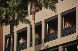 Lidé stojí na balkonu uzavřeného hotelu
