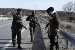Příslušník řecké armády zadržuje migranty na hranicích