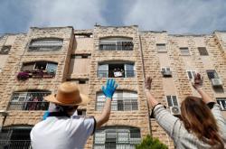 Lidé mávají přeživším holocaustu do oken