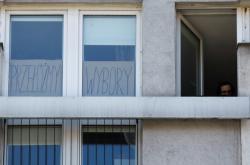 Odložme volby, vyzývá plakát za jedním z oken ve Varšavě