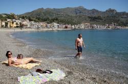 Lidé na pláži na sicilské Taormině
