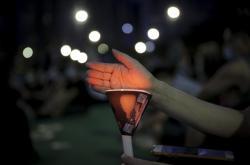 Aktivista během vigilie drží svíčku na památku obětí masakru na náměstí Nebeského klidu