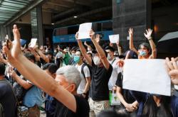 Lidé s prázdnými papíry místo zakázaných sloganů přišli před soud podpořit zatčené aktivisty
