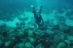 Potápěč plave nad amforami u vraku řecké lodi