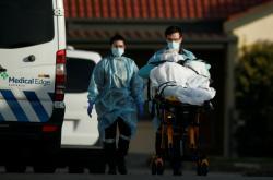 Zdravotníci převážejí nakaženého koronavirem z domova pro seniory v Melbourne