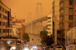 Bay Bridge v San Franciscu na pozadí nebe zbarveného kouřem z požárů