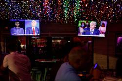 Lidé v restauraci na Floridě sledují souběžné diskuze Bidena a Trumpa s diváky