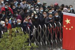 Zaměstnanci letiště Pudong se v rouškách tísní u testovacího centra v Šanghaji