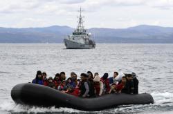 Člun s migranty míří k pobřeží řeckých ostrovů, v pozadí je doprovází plavidlo Frontexu