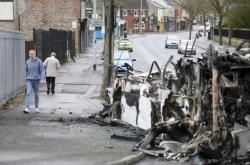 Lidé chodí okolo zničeného autobusu v Severním Irsku