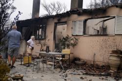 Majitelé obhlížejí zničený dům v obci Drosopigi poblíž Atén