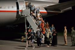 Pasažeři vystupuji na pražském letišti ve Kbelích z českého evakuačního letounu z Kábulu