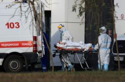 Moskevští zdravotníci převážejí pacienta s koronavirem