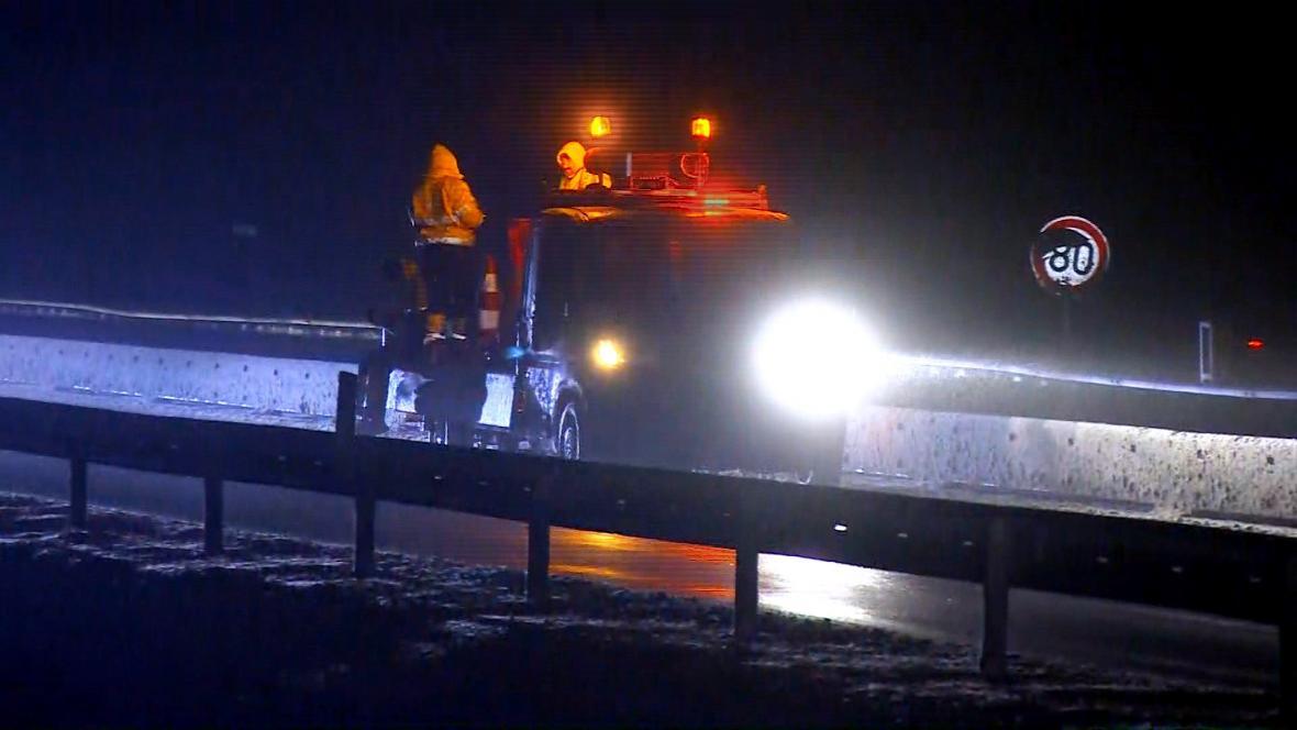 Dělníci rozmísťují dočasné dopravní značení