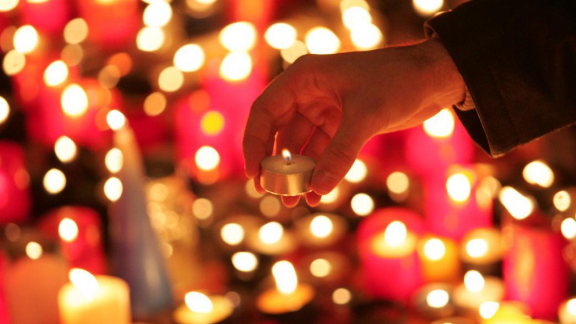 Pražští občané zapalují svíčku jako upomínku na násilný zásah SNB proti studentům