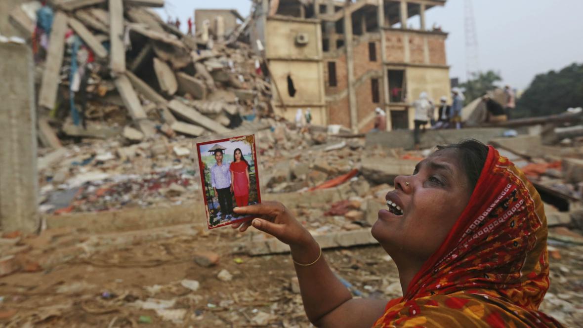 Žena čeká před troskami budovy na zprávy o svých příbuzných