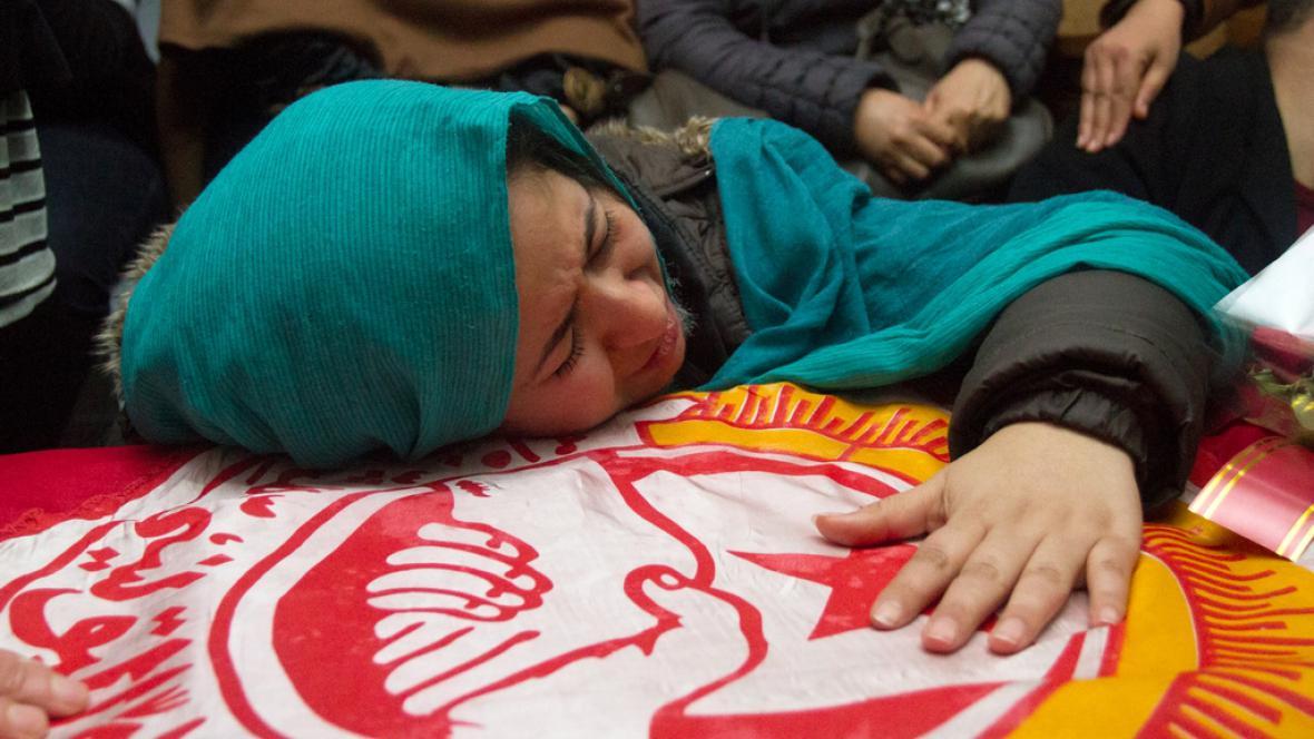 Žena pláče nad rakví Šukrího Bilajda