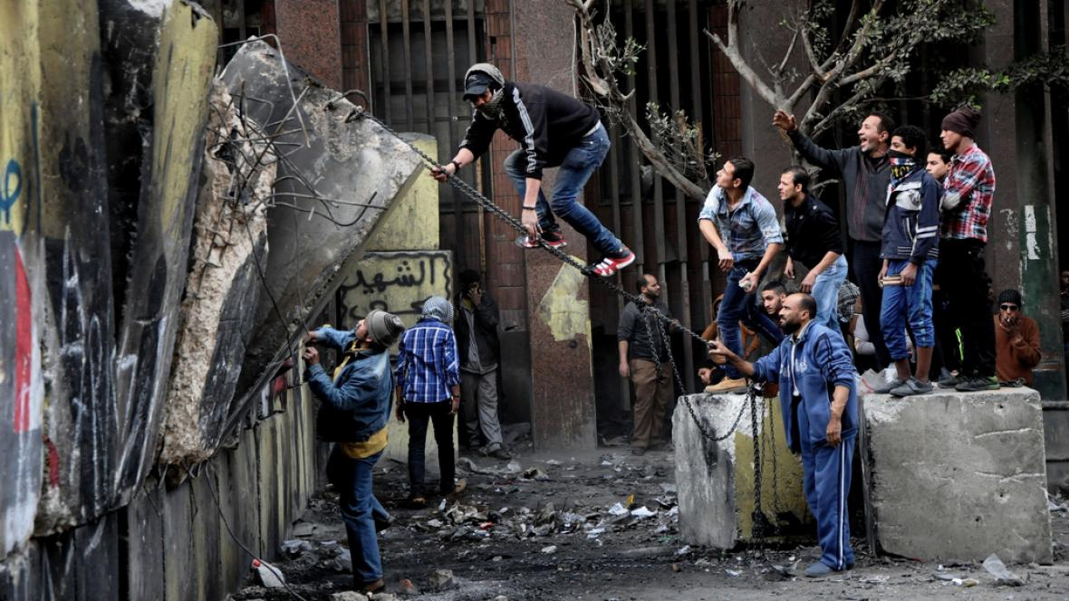 Demonstranti se snaží strhnout zeď u náměstí Tahrír