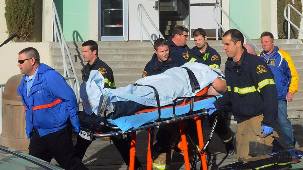 Záchranáři odvážejí postřeleného studenta