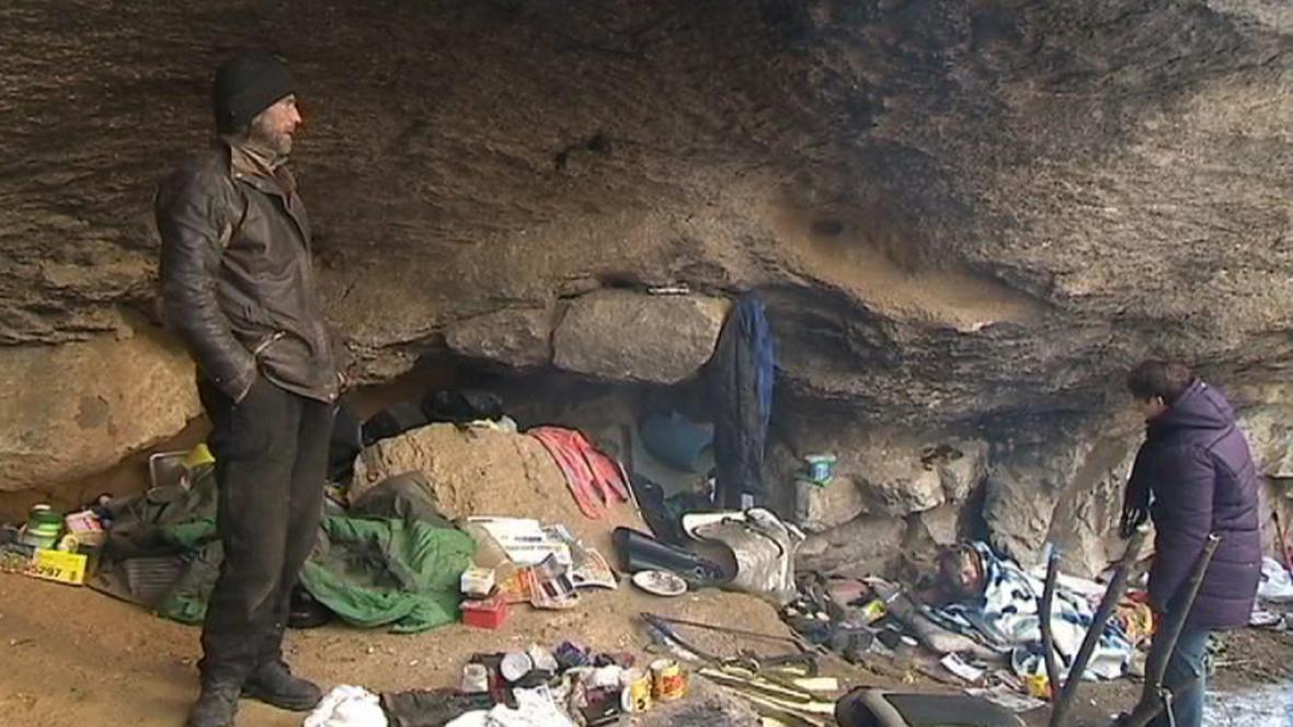 Lidé bez domova pod skalním převisem