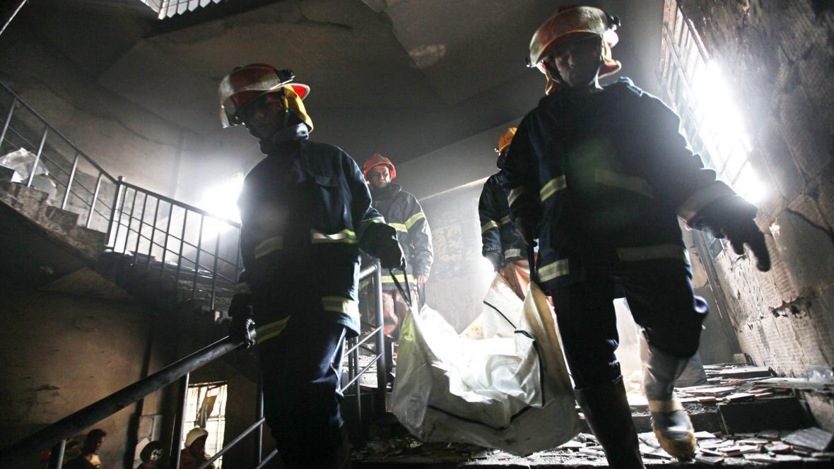 Hasiči odklízejí následky požáru v bangladéšské továrně
