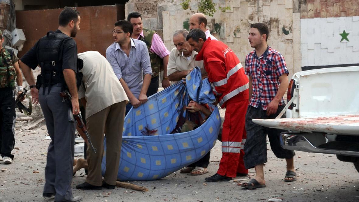Muži odnášejí tělo oběti výbuchu v Aleppu