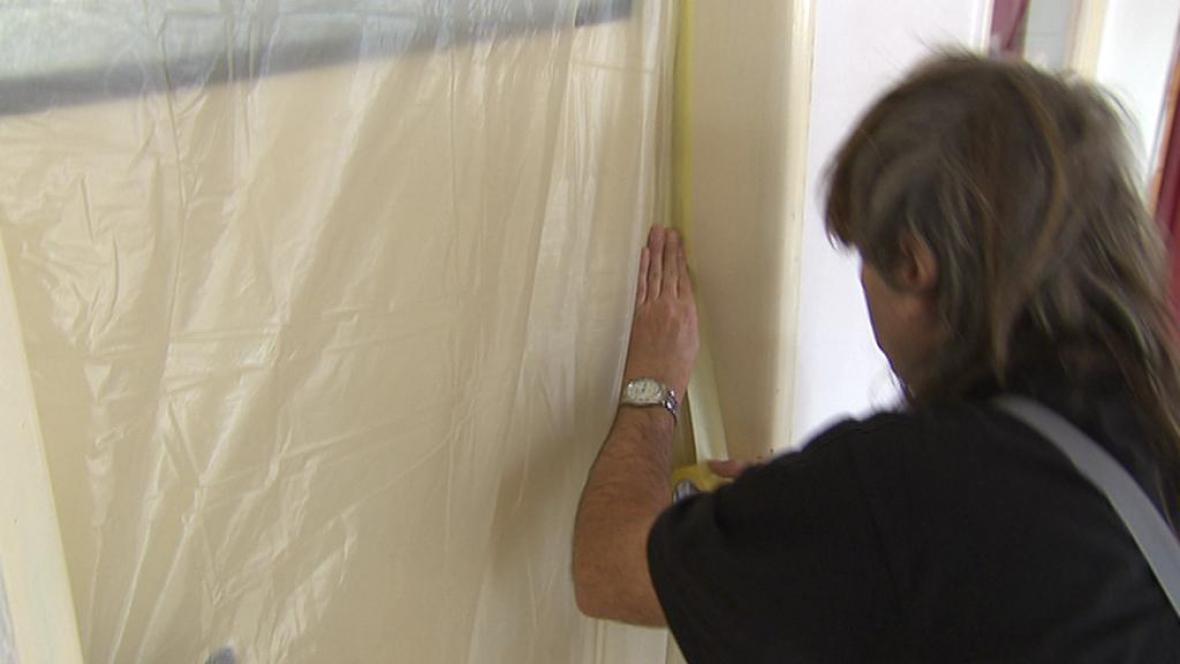 Pracovník utěsňuje dveře před únikem azbestu
