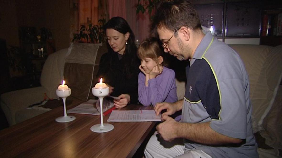 Rodina Andreje Jegošina kontroluje účty při světle svíček