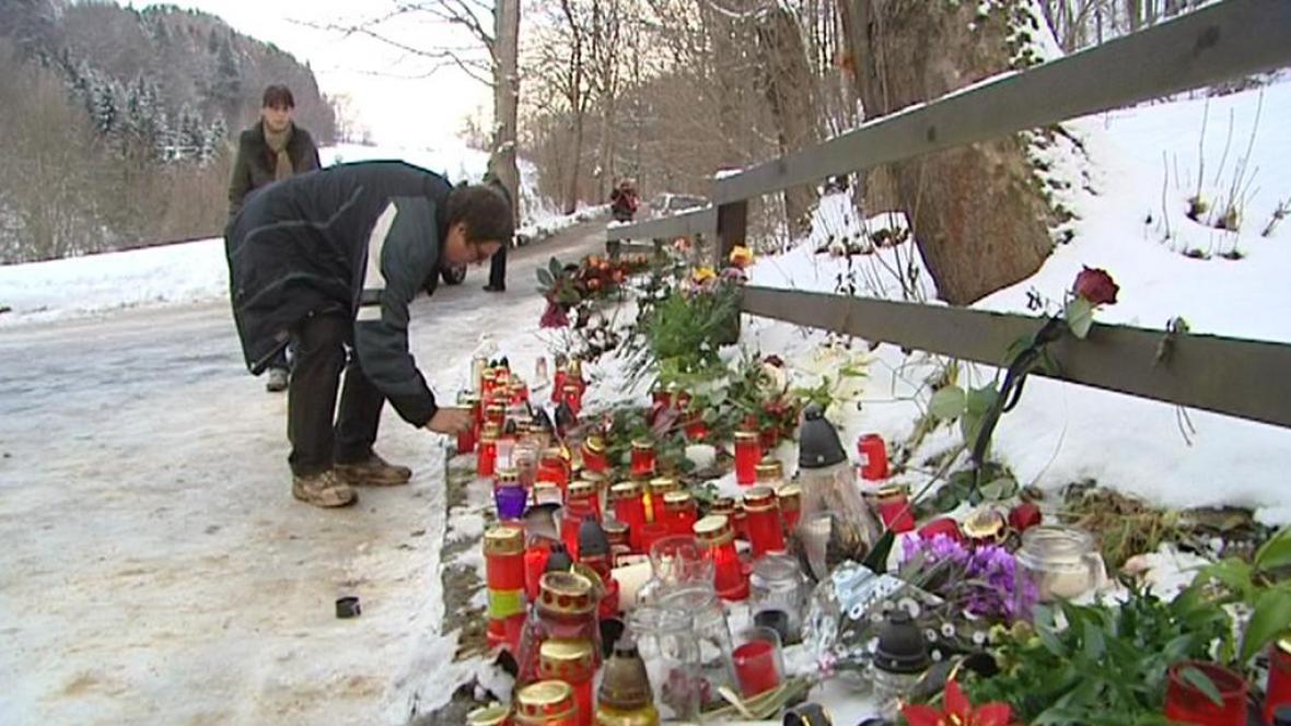 Lidé pokládají svíčky před plot chalupy na Hrádečku