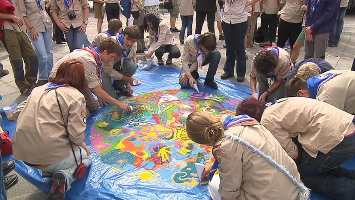 Skauti tvoří barevnou zeměkouli z písku