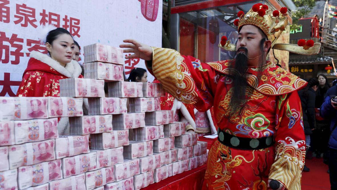 Muž oblečený jako čínský bůh bohatství v rámci oslav jarních svátků