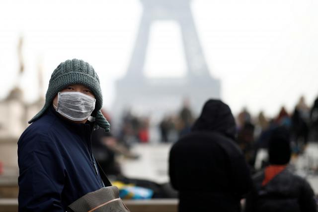 Číňan s maskou před Eiffelovou věží v Paříži