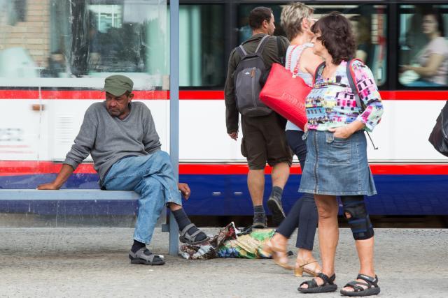 Bezdomovec na tramvajové zastávce v Olomouci