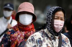 Lidé v Pekingu vycházejí s maskami