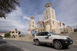 Auto OSN projíždí kolem kostela Agios Georgios, vlevo v pozadí je vidět nedaleká mešita