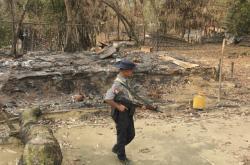 Voják v Myanmaru prochází kolem spáleného domu Rohingů