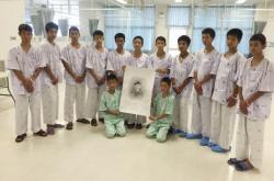 Thajští fotbalisté a jejich trenér pózují s portrétem potápěče, který zahynul při jejich záchraně