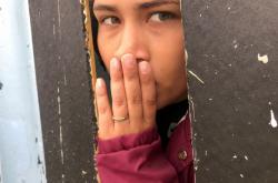 Žena u zdi mezi Mexikem a USA dívající se z Tijuany na druhou stranu hranice