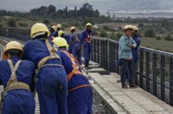 Stavba železničního mostu v Keni. Afričtí dělníci a čínský předák