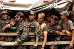 Příslušníci Kosovské osvobozenecké armády (UČK) na korbě nákladního vozu, který je veze do kasáren v Prizrenu (17. 6. 1999)