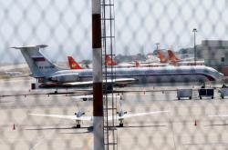 Letadlo s ruskou vlajkou na ocase na letišti v Caracasu